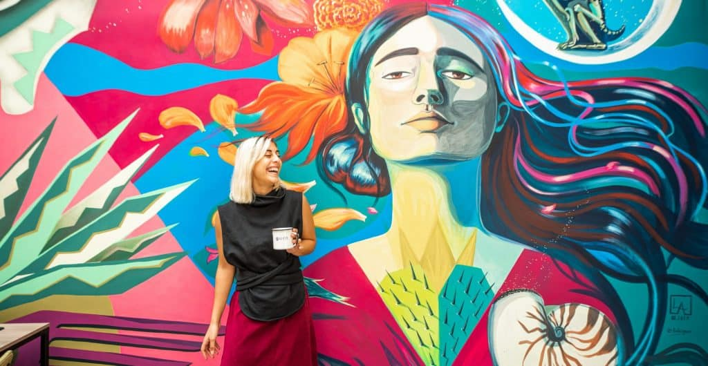 Woman smiling in front of an art wall